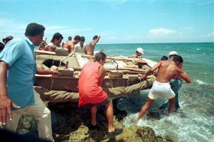 Unidentified Cubans loer a raft into the water in this Aug.19,1994 photo, preparing to leave the Cuban coast in Cojimar, near Havana Cuba during the 1994 massive exodus. In mid-August 1994, after a string of boat hijackings, unprecedented rioting and the killing of a Cuban navy lieutenant prompted President Fidel Castro to suggest that those wanting to leave, could. Over about five weeks, more than 30,000 Cubans took Castro at his word and sailed away on makeshift rafts while authorities stood by.(AP Photo/Jose Goitia,)